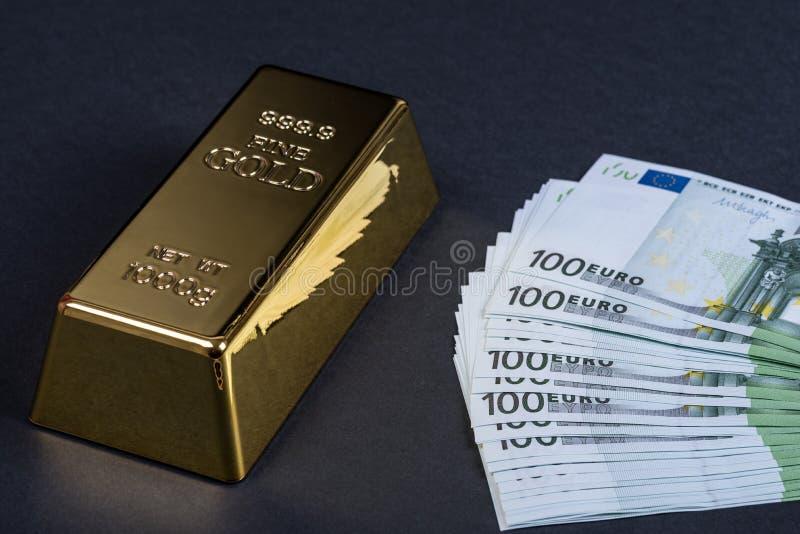 Eurokassa och guld- stång på en svart bakgrund Sedlar pengar bili tacka guldtacka arkivfoton