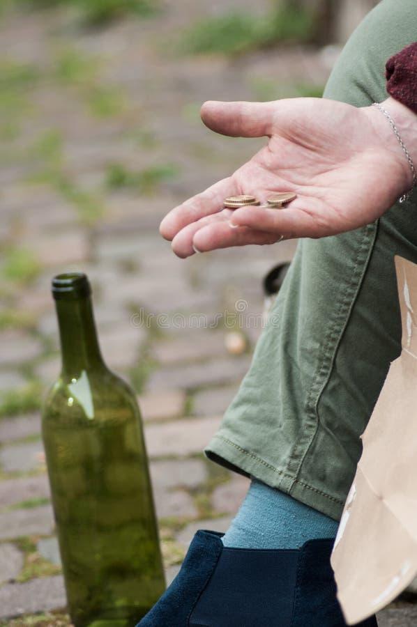 Euromünzen in der Hand von den Armen, die in der Straße mit Rebflasche sitzen lizenzfreies stockbild