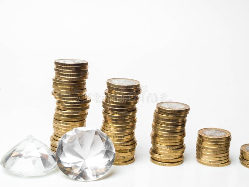 Euromünzen, Diamanten, die auf weißer Tabelle liegen lizenzfreie stockbilder