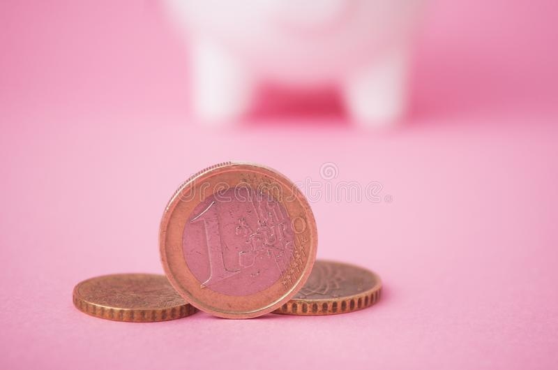 Euromünzen vor gelbem Sparschwein auf grünem Hintergrund lizenzfreie stockfotos
