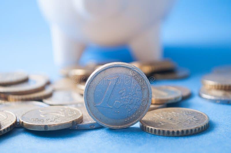 Euromünzen vor weißem Sparschwein auf blauem Hintergrund lizenzfreies stockfoto
