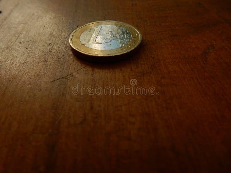 1 euromynt på gammal trätabellbakgrund royaltyfri fotografi