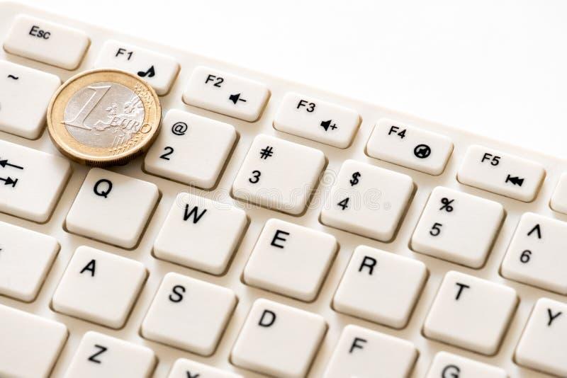 Euromyntet ligger på datortangentbordet för nummer ett Begreppsmässig bild på ämnet av finans och datateknik Hur man gör arkivbilder