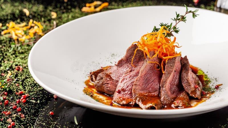Europäische Küche Mariniertes Kalbfleisch mit dem Braten halb gar Röstgrad Chef gießt Olivenöl des Rindfleisches Servierteller lizenzfreies stockbild