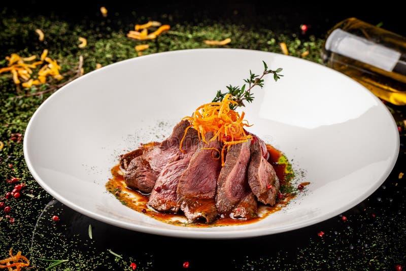 Europäische Küche Mariniertes Kalbfleisch mit dem Braten halb gar Röstgrad Chef gießt Olivenöl des Rindfleisches Servierteller stockbilder