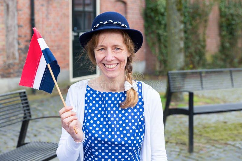 Europäische Frau, die Befreiung mit niederländischer Flagge feiert lizenzfreie stockfotos