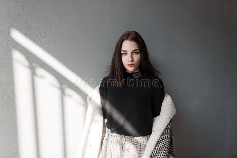 Europäische junge brunette Frau mit natürlichem Make-up in einer karierten Jacke des Retrostils in einem Hemd in den Hosen steht  lizenzfreie stockfotografie