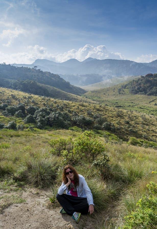 Europäische junge touristische Frau, die auf dem Gras am schönen Tal umgeben durch Berge sitzt lizenzfreie stockfotografie