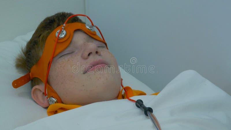Europäische Kinderführungselektroenzephalographie Ein Prozessfragment Rheoencephalography - ein Doktor befestigt Elektroden an stockfotografie