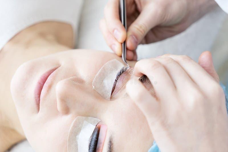 Europäische Schönheit erhält lamellierendes Verfahren der Behandlung für ihre Wimpern im Schönheits- und Wellnesssaal lizenzfreie stockfotos