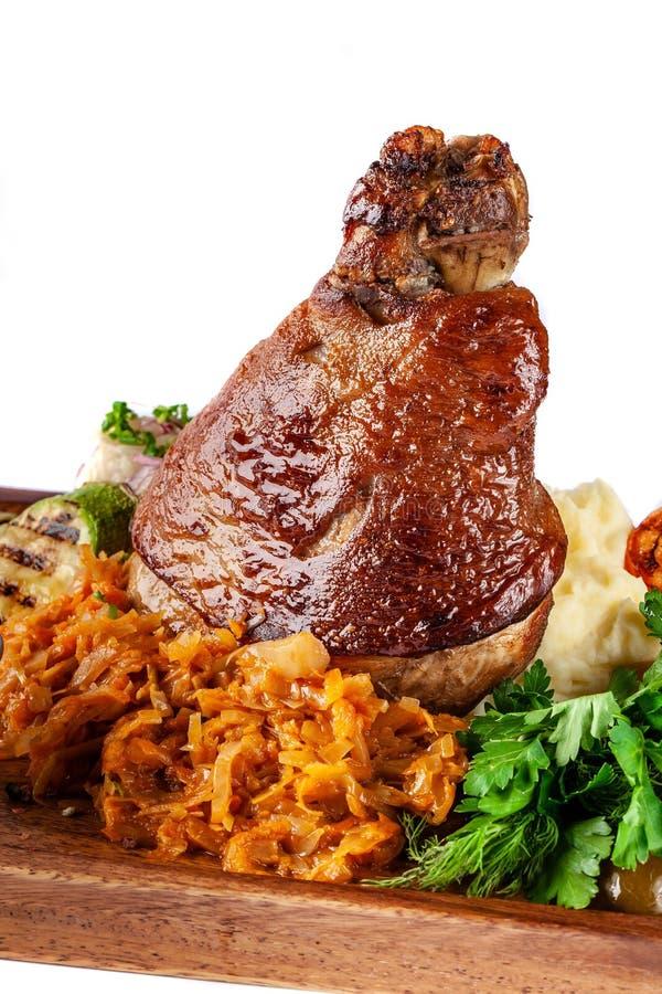 Europäische, tschechische Küche Schweinefleischknöchel auf einem hölzernen Brett mit Kartoffelpürees, gedämpfter Kohl, gegrilltes stockfotografie