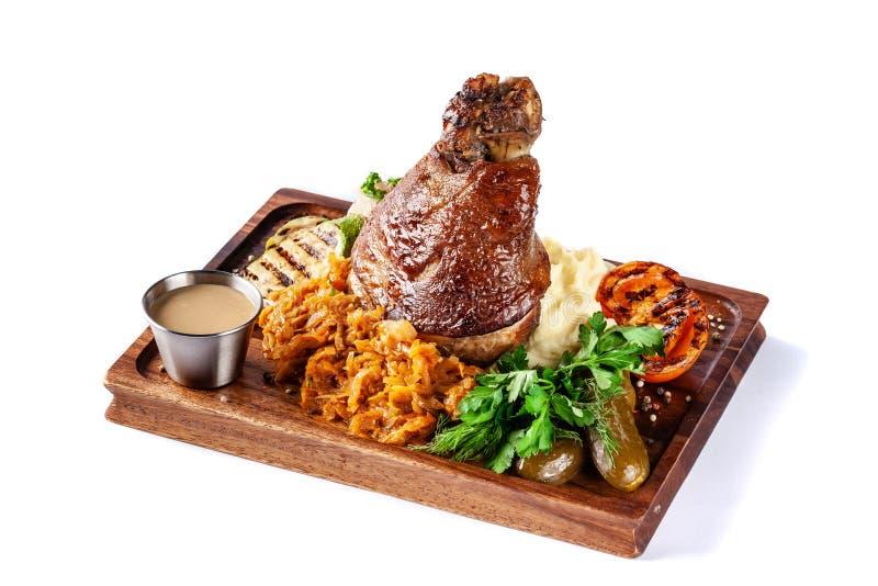 Europäische, tschechische Küche Schweinefleischknöchel auf einem hölzernen Brett mit Kartoffelpürees, gedämpfter Kohl, gegrilltes lizenzfreies stockfoto