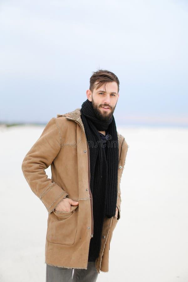 Europäischer gutaussehender Mann mit dem tragendem Mantel und Schal des Bartes, die im weißen Schneehintergrund stehen stockfotografie