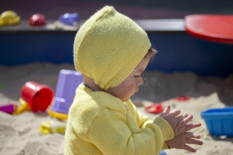 Europäischer Kindermädchenjunge rüttelt seine Hände vom Sand im Sandkasten Einjähriges Spielen des Kinderbabys auf dem Spielplatz lizenzfreie stockbilder