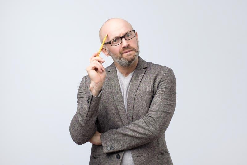 Europäischer Mann denkt an etwas, das sein Gesicht mit Bleistift verkratzt lizenzfreie stockfotos