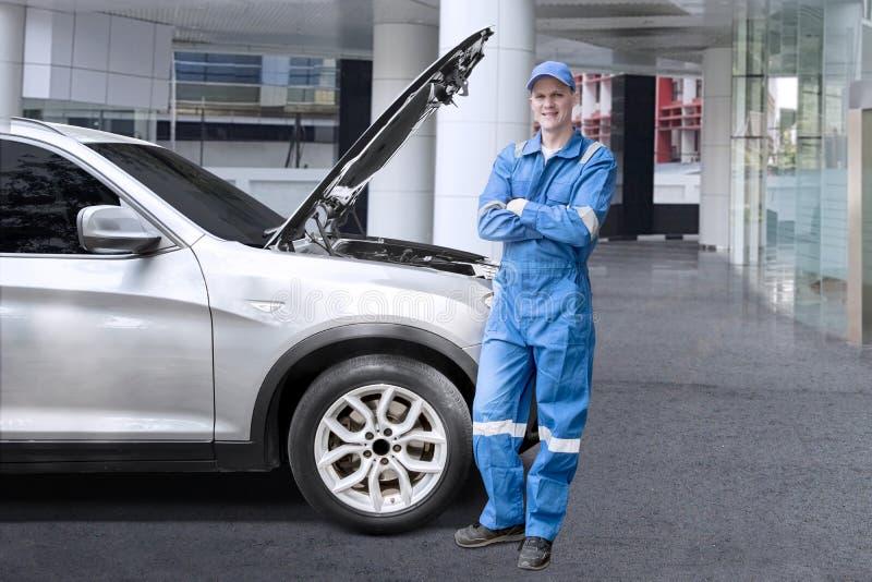 Europäischer Mechaniker, der nahe einem defekten Auto steht stockbilder