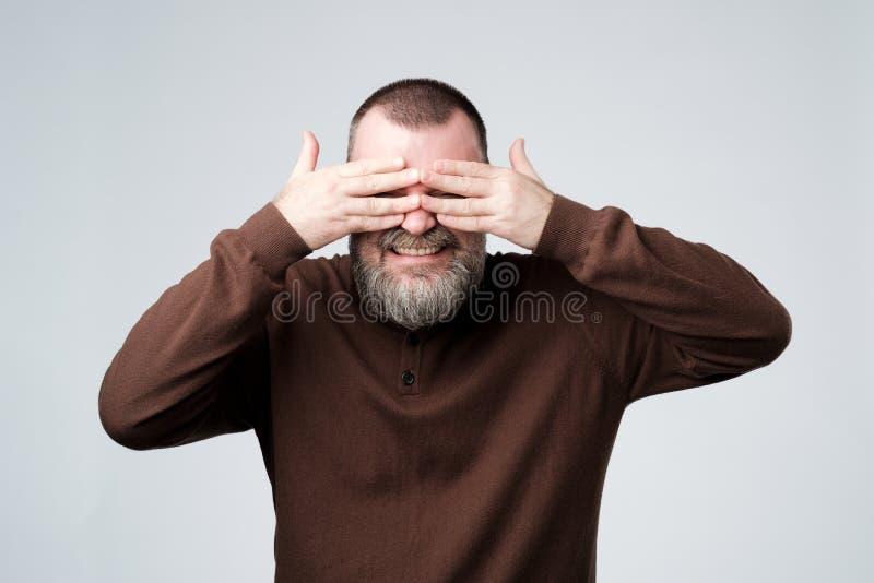 Europäischer reifer Mann, der sein Gesicht durch Hände bedeckt lizenzfreie stockbilder