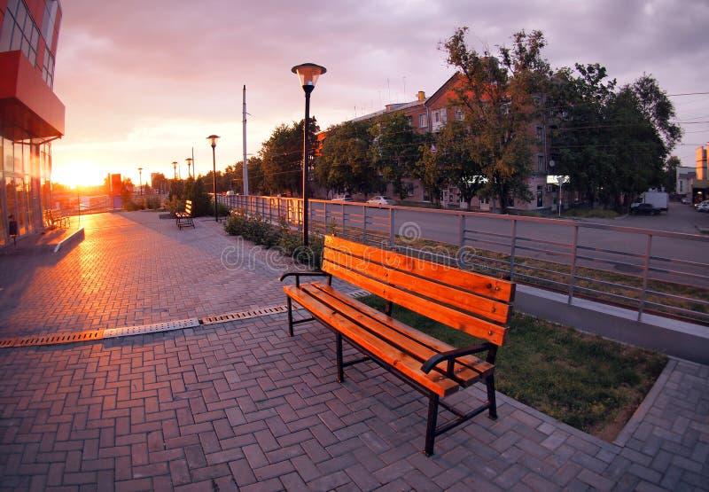 Europäischer städtischer Bürgersteig, Bänke und Laternen am Abend lizenzfreies stockbild
