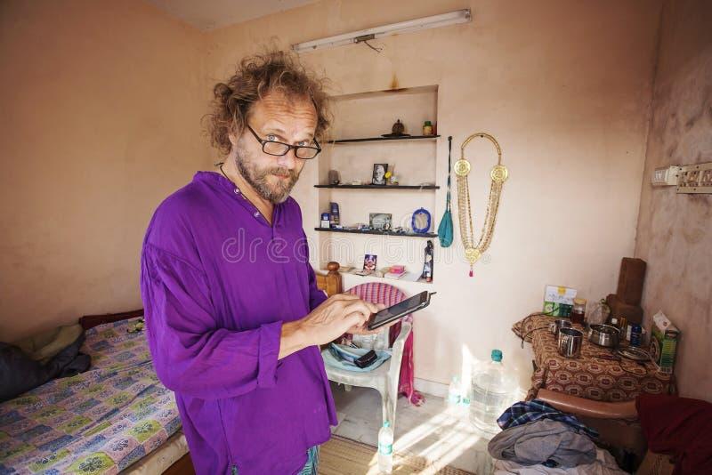 Europäischer Sucher in seiner Mietwohnung nah an Arunachala-Berg, der sein Mobiltelefon betrachtet stockbilder