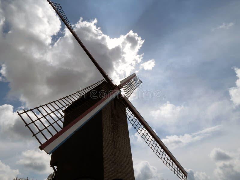 Europa, België, West-Vlaanderen, Brugge, oude windmolen op de achtergrond van de overweldigende hemel stock afbeelding