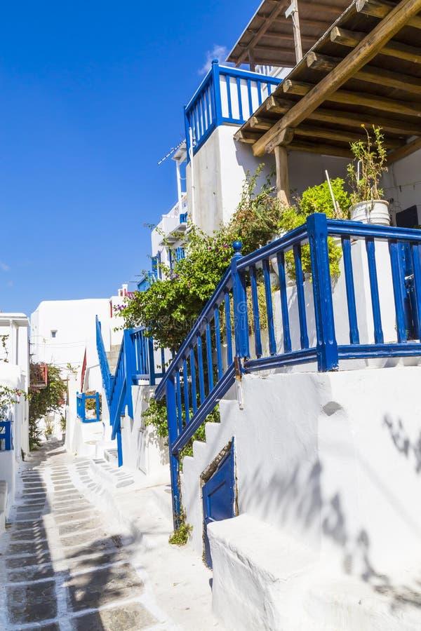 Europa Grekland cyclades Mykonos ö En borggård på den traditionella smala gatan med den blå dörren, fönster och balkong och vit royaltyfri fotografi
