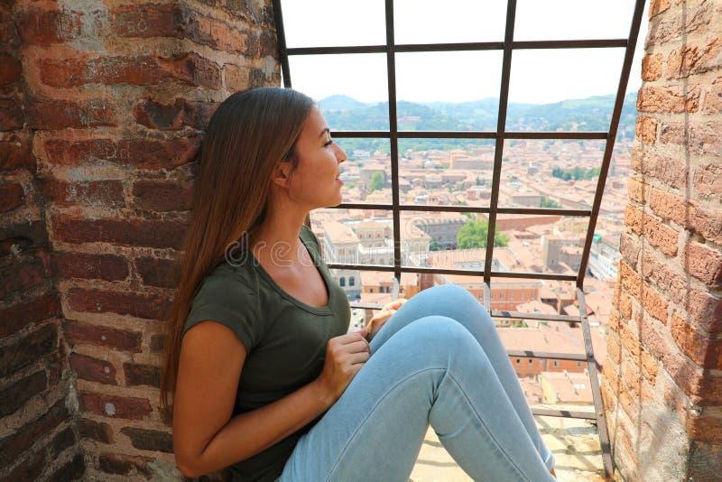 Europa loppkvinna som uppifrån ser Bolognacityscape av det Asinelli tornet, berömd medeltida turist- dragning i Italien royaltyfria bilder