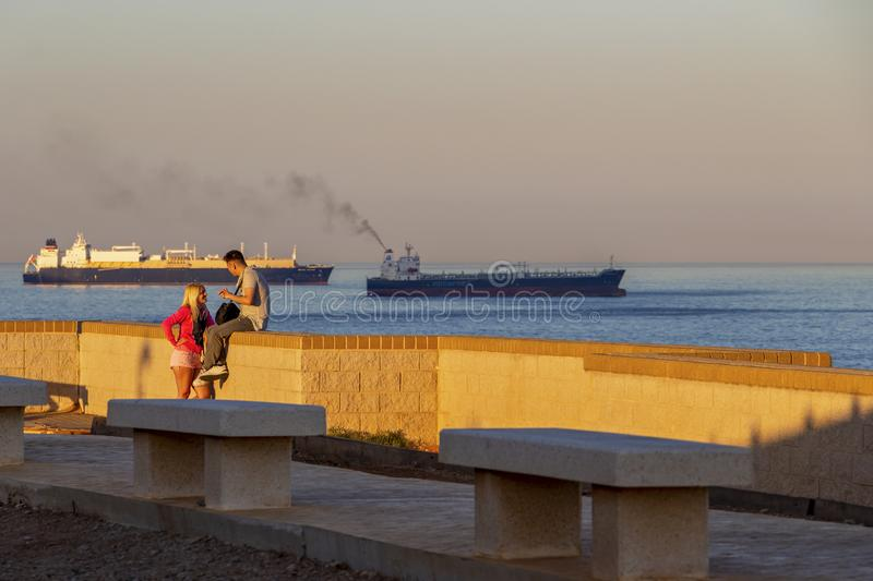 Europa Point view in Gibraltar. GIBRALTAR, UNITED KINGDOM - MAY 26, 2019: Young couple at the Europa Point Lighthouse, two container ships in the background stock photography