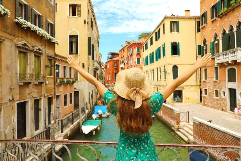 Europa-Reiseferienspaß-Sommerfrau mit den Armen up und der Hut, der in Venedig, Italien glücklich ist Sorgloser Mädchentourist im stockfotos