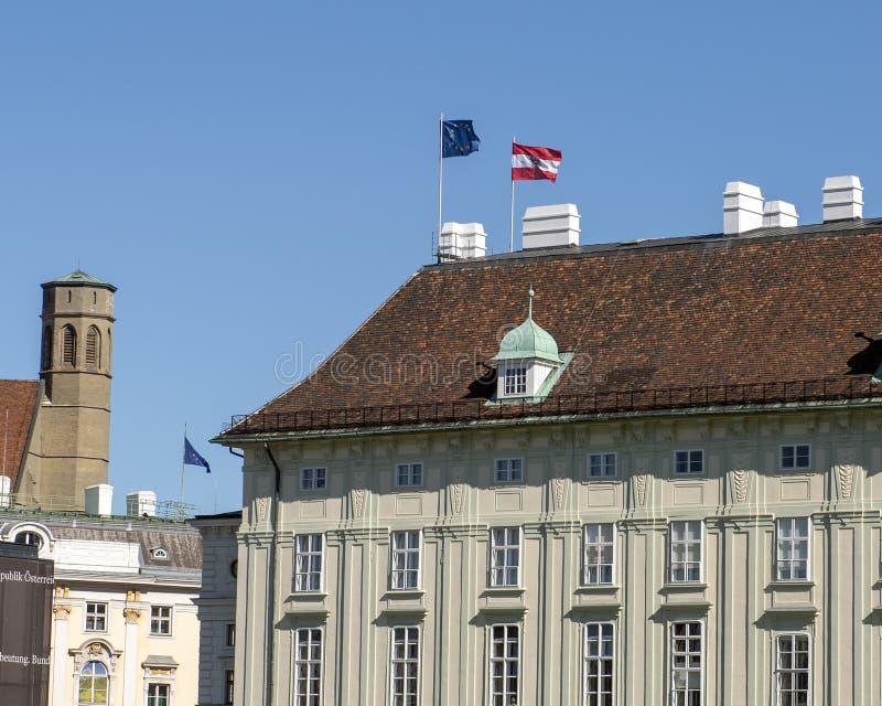 Europa und österreichische Flaggen, die auf die Dachspitze eines Gebäudes in Hofburg-Palast, Wien, Österreich fliegen stockfotos
