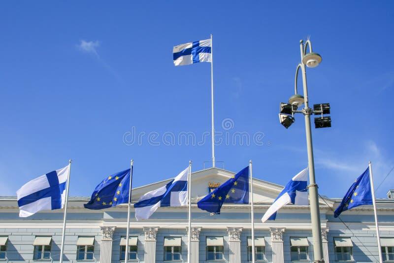 Europas och Finlands flaggor som tillsammans viftar med presidentpalatset i Helsingfors royaltyfria bilder