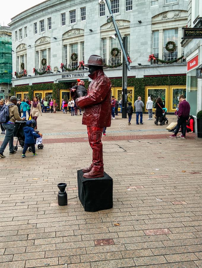 Europe. Culture. Street Artists. Street actor on a basement animates a square in Cork, Ireland, interpreting the living statue of a fireman who offers a child stock image