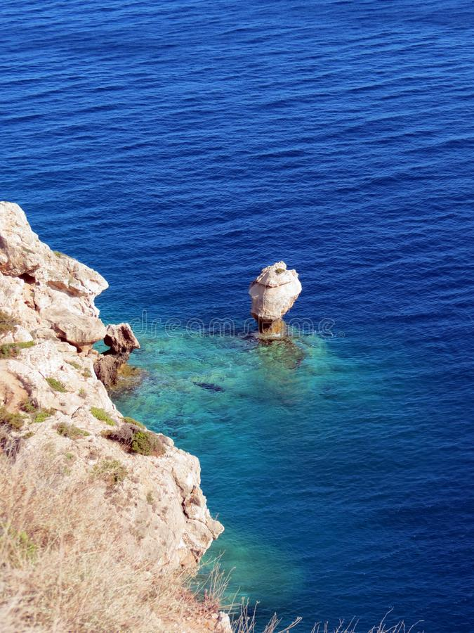 Greece, Acre of Ireo, waves slowly erode a lonely rock. Europe, Greece, Acre of Ireo, waves slowly erode a lonely rock in the Gulf of Corinth stock images