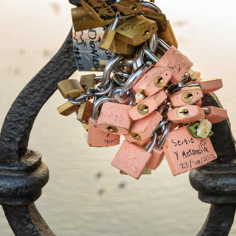 Europe love padlock tradition. ROME - OCTOBER 5, 2012: Colorful pink padlocks adorn railings on bridge across the Tiber River. Couples and families attach stock photo