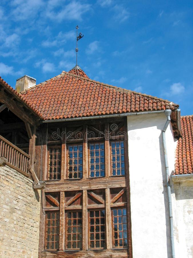 Europe. Part of the old medieval building: the roof covered by red shingles and wooden frame for windows, and white wall of the ho royalty free stock images