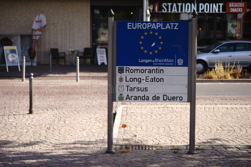 Europe Square Langen. Langen, Germany - October 06, 2018: The coats of arms and names of the twin cities of Langen on a sign of Europe Square on 06 October 2018 stock photography