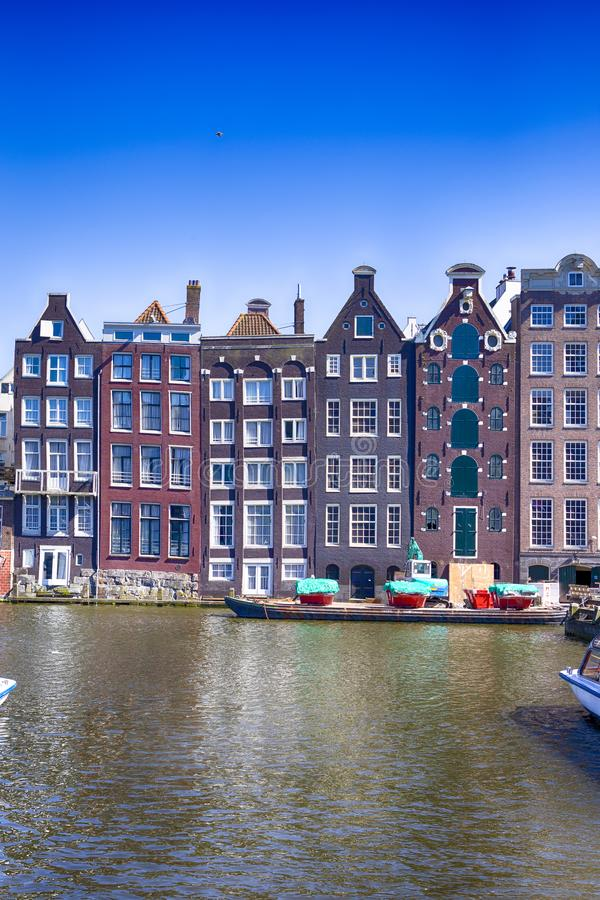 Europe Travel Concepts and Ideas. Row of Traditional Ancient Houses At Damrak Canal in the Capital of The Netherlands in Amsterdam. Vertical Image Orientation royalty free stock images