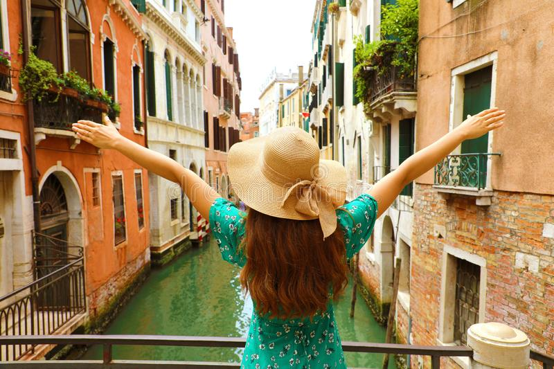 Europe travel vacation fun summer woman with arms up and hat hap. Py in Venice, Italy. Carefree girl tourist in European destination wearing green fashion dress royalty free stock photography