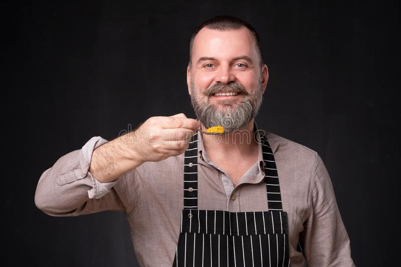 Europeam mature chef showing his favorite spice, orange turmeric royalty free stock photography