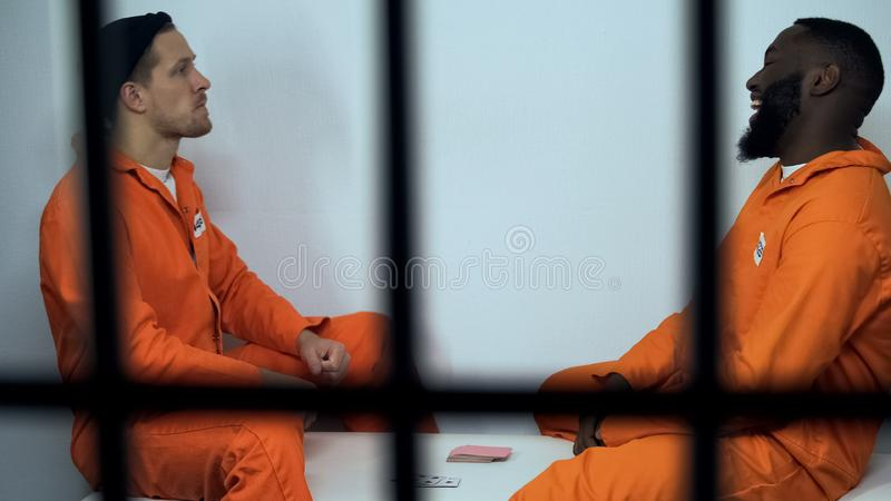 European and african-american inmates playing cards in cell, illegal activity. Stock photo stock image