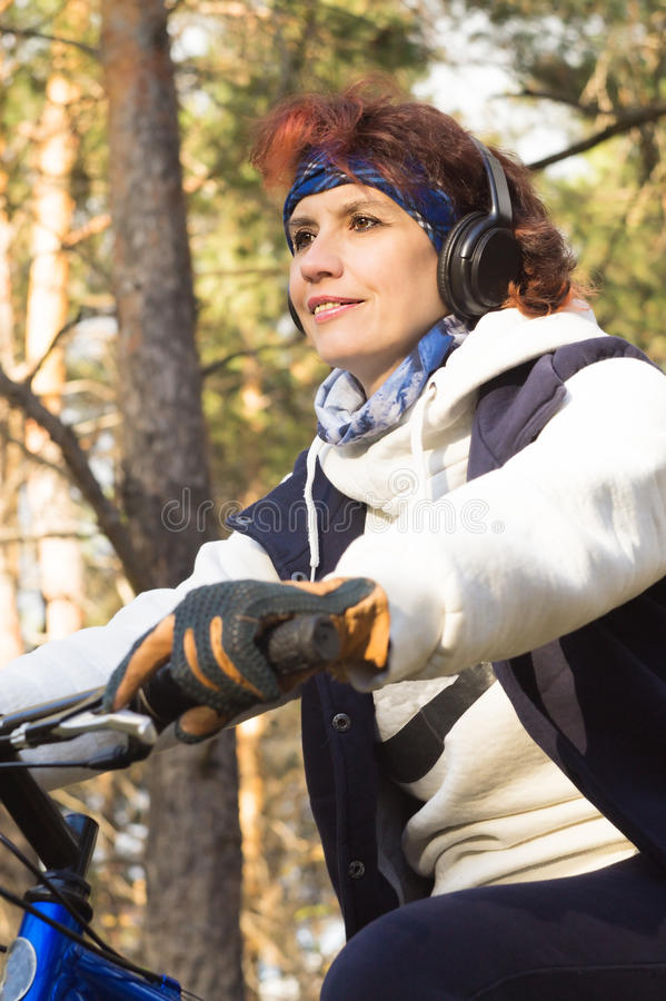 European attractive woman in headphones in autumn forest on the royalty free stock photos