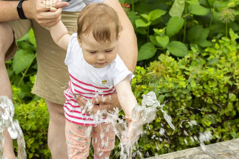 European baby girl playing with jets of water in a fountain. Baby wets her hands in the fountain. Caucasian girl playing with. Water, closeup portrait of a stock image