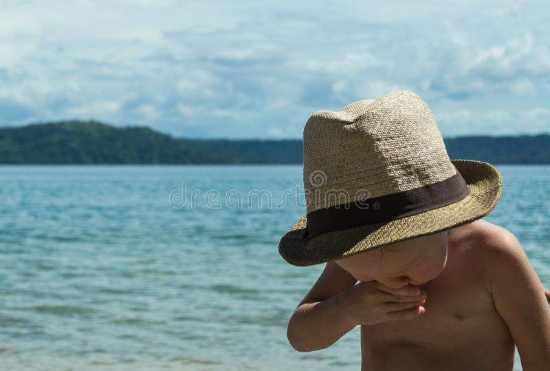 European Toddler sneezes, on the background of the sea. Child was sick on holiday stock image