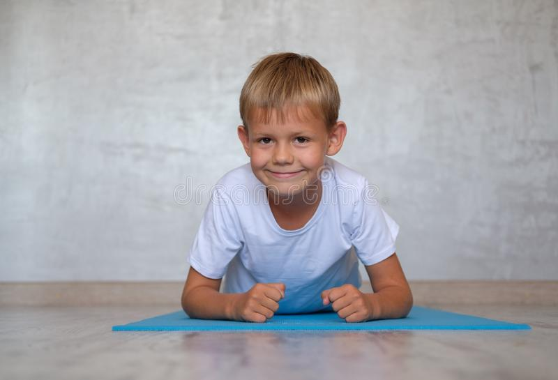 European boy with a smile performs plank exercise on the Mat royalty free stock photography