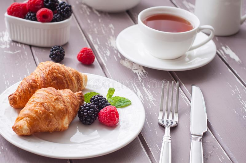 European breakfast tea coffee milk croissant fresh berries morning. European breakfast with fresh berries on the wooden background. Toned stock image