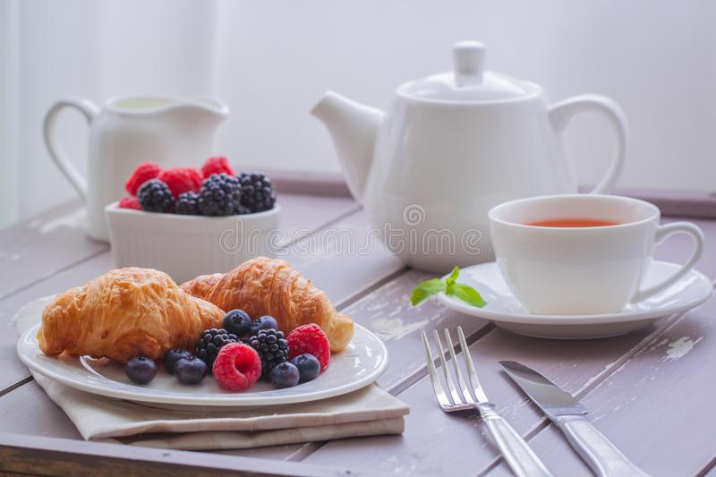 European breakfast tea coffee milk croissant fresh berries morning. European breakfast with fresh berries on the wooden background. Toned royalty free stock photos