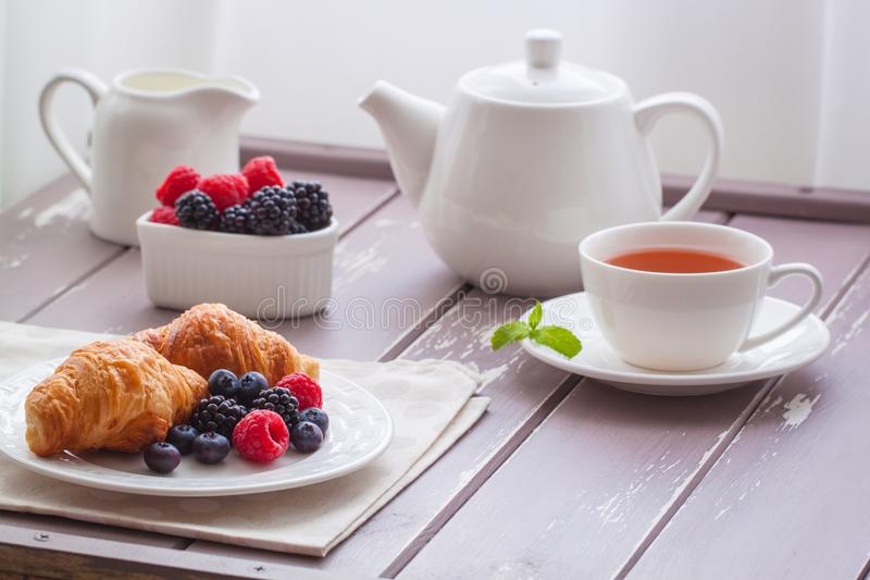 European breakfast tea coffee milk croissant fresh berries morning. European breakfast with fresh berries on the wooden background. Toned stock photo