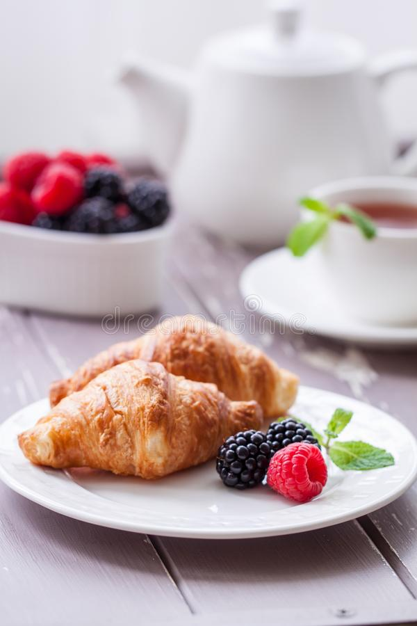 European breakfast tea coffee milk croissant fresh berries morning. European breakfast with fresh berries on the wooden background. Toned stock images