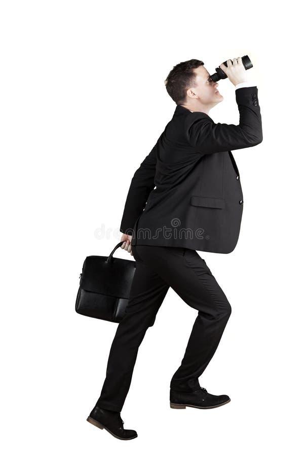 European businessman posing to step upward. European businessman holding a binocular and suitcase while posing to step upward, isolated on white background stock photography