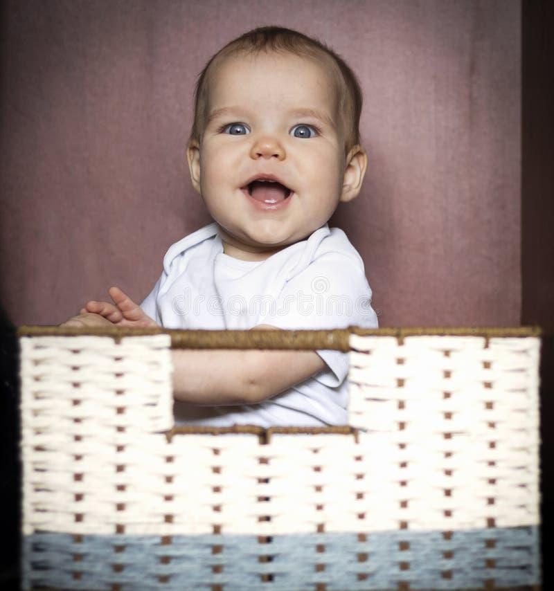 European Caucasian Joyful child, kid, girl, boy smiling and sits in box in wicker basket In closet for storage on dark. European Caucasian Joyful child, kid stock photo