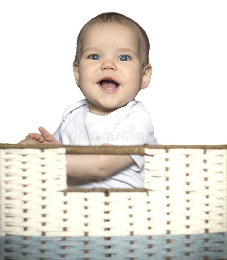 European Caucasian smiling child, kid, girl, boy sits in a box in a wicker basket on white isolated background. Concept royalty free stock photography